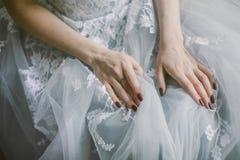 Händer av sammanträdebruden i en grå färg snör åt klänningen brud- mode Royaltyfri Foto