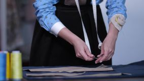 Händer av skräddaren som arbetar med modeller på tyg stock video