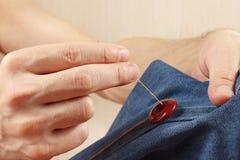 Händer av skräddaren syr upp en knapp till grov bomullstvilltygslutet royaltyfria bilder