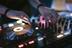 Händer av styrning för spåret för kvinnadiscjockeynypen olik på dj-` s pryder på nattklubben Royaltyfri Fotografi