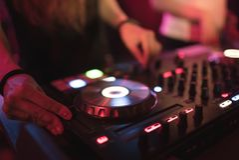 Händer av styrning för spåret för kvinnadiscjockeynypen olik på dj-` s pryder på nattklubben Royaltyfria Foton