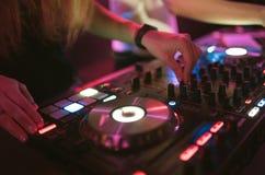Händer av styrning för spåret för kvinnadiscjockeynypen olik på dj-` s pryder på nattklubben Fotografering för Bildbyråer