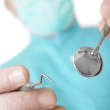 Händer av tandläkaren med en spegel och en krok arkivfoton