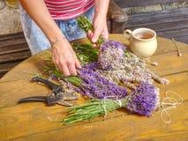 Händer av trädgårdsmästarekvinnan skapar den växt- buketten för den avslappnande lukten arkivfoto