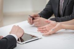 Händer av tre och två affärsmän som diskuterar affärsangelägenheter Arkivbild