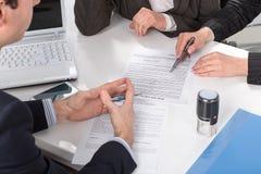 Händer av tre personer, undertecknande dokument Arkivfoton