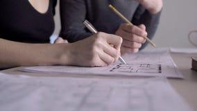 Händer av två arkitekter som arbetar på byggnad, gör en skiss av, stänger sig upp stock video