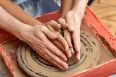 Händer av två personer skapar krukan, hjul för keramiker` s Undervisningkrukmakeri Arkivfoto