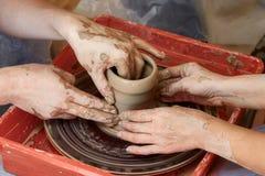 Händer av två personer skapar krukan, hjul för keramiker` s Undervisningkrukmakeri Arkivbild