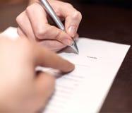 Händer av två personer undertecknade dokumentet Arkivfoton