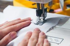 Händer av unga flickan på symaskinen Royaltyfri Foto