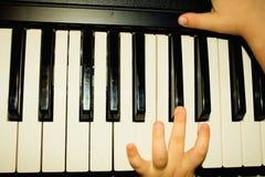 Händer av ungen som som spelar pianot arkivfoto