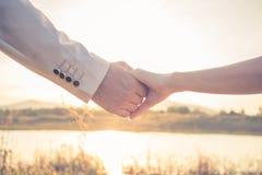 Händer av vännen på solnedgången Arkivfoto