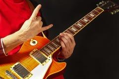 Händer av vaggar gitarristen som spelar den elektriska gitarren på mörk bakgrund Arkivbilder