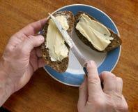 Händer, baktalar grovt smör ett smör på en smörgås Arkivfoton