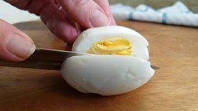 Händer baktalar snittet ett ägg på ett träbräde stock video