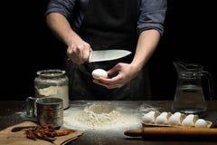 Händer bryter ett ägg in i mjöl för att göra deg royaltyfria bilder