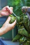 Händer drar åt raden för att göra Zongzi, ris Dumplingrs för traditionell kines royaltyfri foto