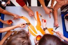 Händer drar på affischen, begreppet av teamwork arkivfoto
