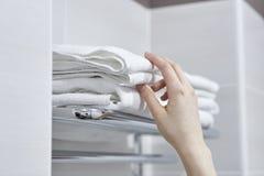 Händer en kvinna tar handdukar i badrummet royaltyfri foto