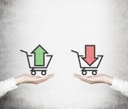Händer erbjuder valet - 'sälj eller köp', Korg av godor arkivbild