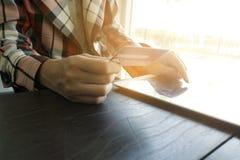 Händer för affärs` som s rymmer en kreditkort och använder den smarta telefonen för Arkivfoto