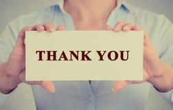 Händer för affärskvinnan som rymmer tecknet eller kortet med meddelandet, tackar dig Royaltyfri Bild