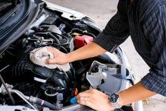 Händer för arbetare för för man som eller automatisk mekaniker gör ren bilmotorn med tyg arkivbild