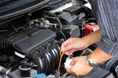 Händer för arbetare för för man som eller automatisk mekaniker kontrollerar det bilmotoroljan och underhållet, innan att resa för arkivbilder