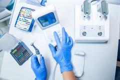 Händer för assistent` s konfigurerar tand- utrustning i kontor för tandläkare` s Nära övre, selektivt fokuserar dentistry Royaltyfri Fotografi