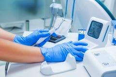 Händer för assistent` s konfigurerar tand- utrustning i kontor för tandläkare` s Nära övre, selektivt fokuserar dentistry Royaltyfria Foton