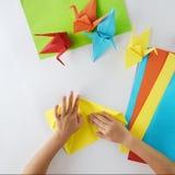 Händer för barn` s gör origami från kulört papper på vit bakgrund Kurs av origami Arkivbilder