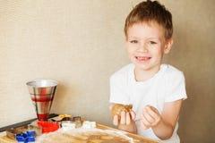 Händer för barn` s gör pepparkakan Bitande kakor för liten pojke för Arkivfoto