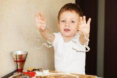 Händer för barn` s gör pepparkakan Bitande kakor för liten pojke för Royaltyfria Bilder