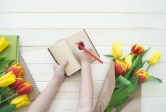Händer för barn` s skriver i en anteckningsbok En bokstav till min moder från barnet Royaltyfria Foton
