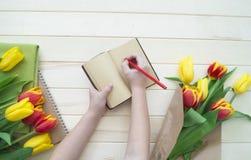 Händer för barn` s skriver i en anteckningsbok En bokstav till min moder från barnet Fotografering för Bildbyråer