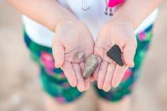 Händer för barn` som s rymmer våt kiselsten- och havstrumpetsnäcka, beskjuter på stranden vid havet Lycklig lek för barn` som s ä arkivfoto
