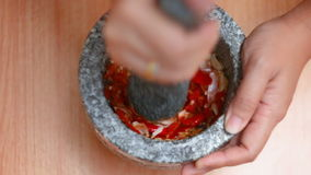 Händer för den bästa sikten av kvinnan som stansar den glödheta nya chili och vitlök med mortelstenen, förbereder blandande örtsm stock video