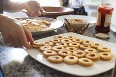 Händer för en kvinna som blandar ingredienser som rå ägg, mjöl, pulver smör och vitt socker på en stor platta för keramik som gör royaltyfri bild