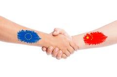 Händer för europeisk union som och Kina skakar med flaggor Fotografering för Bildbyråer