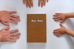 Händer för familjbibel Arkivfoton