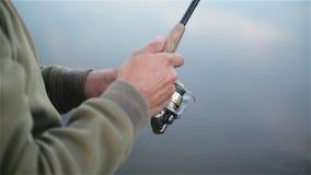 Händer för fiskare` s rymmer metspöet Plan för närbild för spole` s stock video