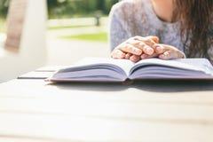 Händer för flicka` s på boken på en tabell parkerar in Läsa i en parkera royaltyfri fotografi