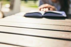 Händer för flicka` s på boken på en tabell parkerar in Läsa i en parkera arkivbilder