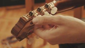 Händer för gitarrist` som s trimmar gitarren arkivfoto