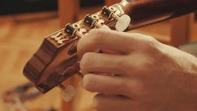 Händer för gitarrist` som s trimmar gitarren arkivbild