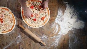 Händer för kock` s i köket som sätter ingredienserna på pizza Pizzabegrepp Produktion och leverans av mat överkant lager videofilmer