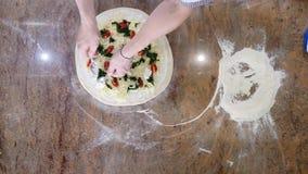 Händer för kock` s i köket som sätter ingredienserna på pizza Pizzabegrepp Produktion och leverans av mat överkant arkivfilmer