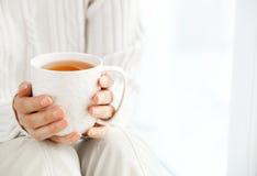 Händer för kvinna` s är den hållande varma koppen kaffe eller te i morgonen su Arkivfoto