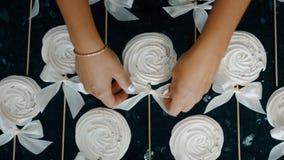 Händer för kvinna` s band en pilbåge på ett antal maräng på en pinne stock video